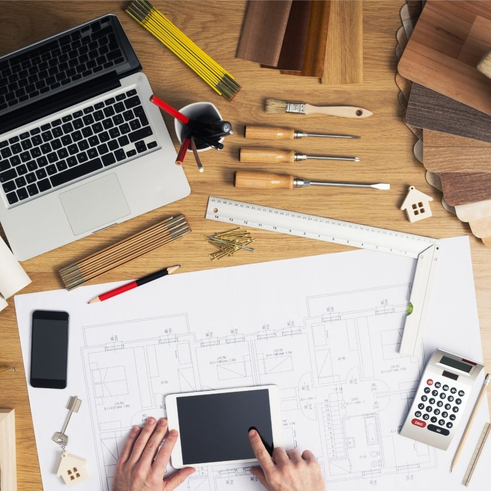 A desktop with a laptop, calculator, home remodeling tools, house plan sketch